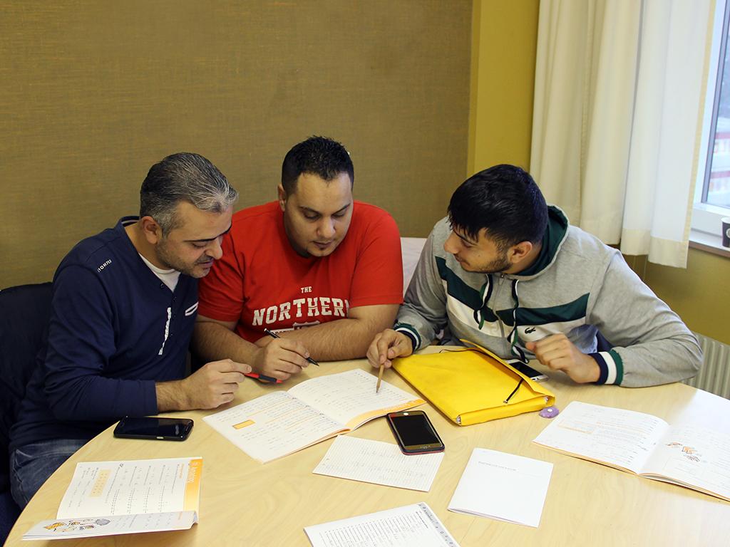 Tre elever sitter och jobbar med text.