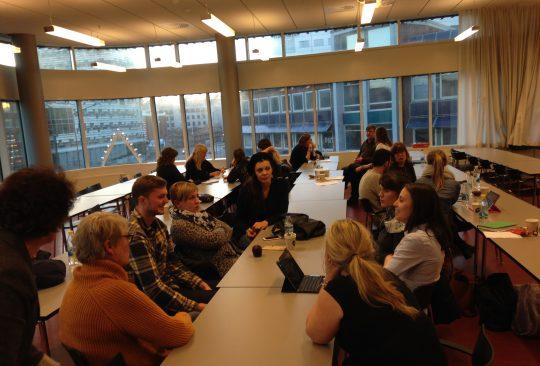 Människor sitter runt bord och samtalar.