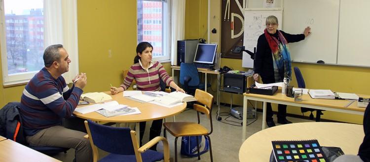 Två elever och en lärare vid tavlan.