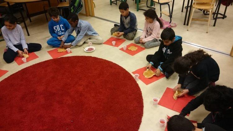 Barn sitter i cirkel med varsin våffla.