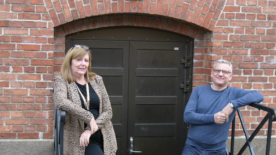 Kvinna och man står i trappan ner till källare.