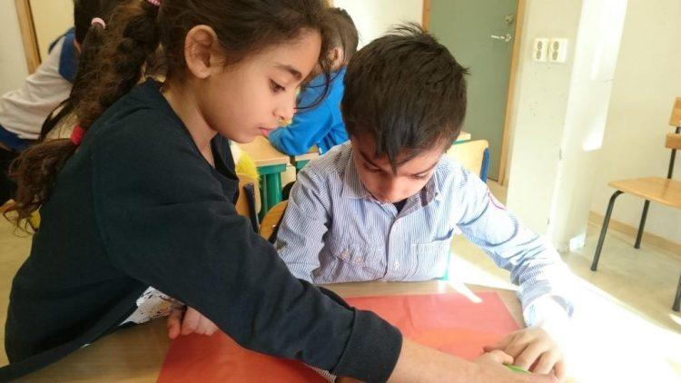 Barn hjälps åt med att skriva.
