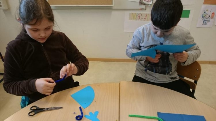 Barn klipper i papper.