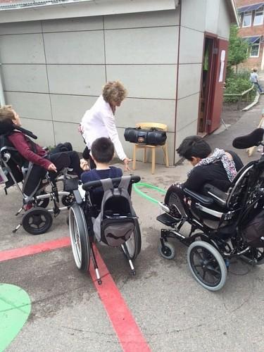 Tre barn i rullstol på skolgård.
