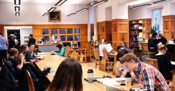 Studenter sitter i bibilotek.