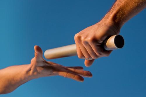 Hand lämnar över stafettpinne till annan hand.
