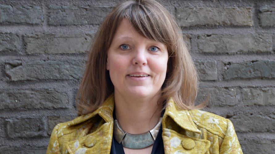 Charlotte Löfqvist framför tegelvägg.