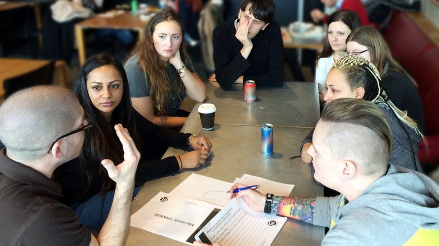 Studenter sitter runt bord.