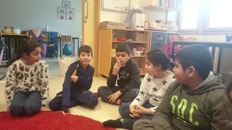 Elever sitter i grupp på golvet.