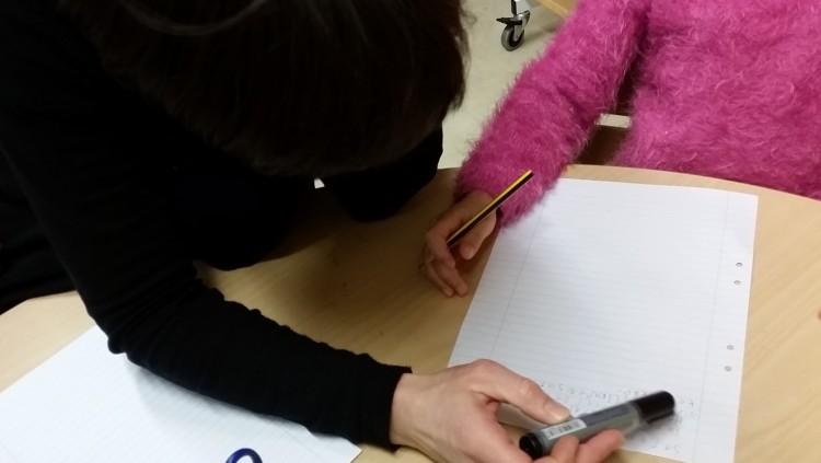 Elever skriver på papper.