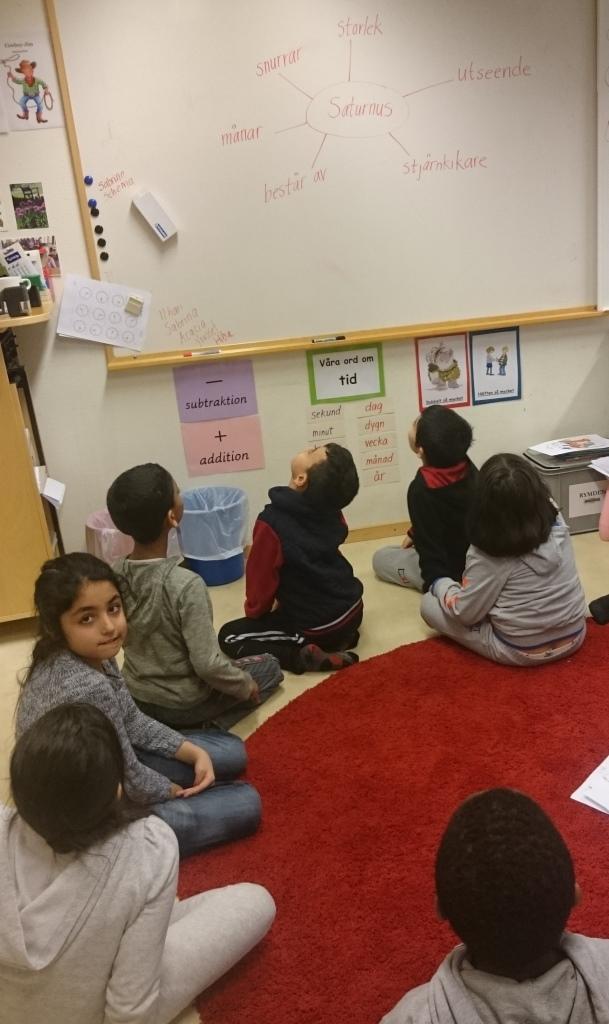 Elever sitter samlade på golvet.