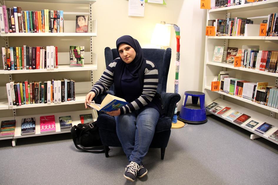 Amina sitter i läsfåtölj med uppslagen bok.