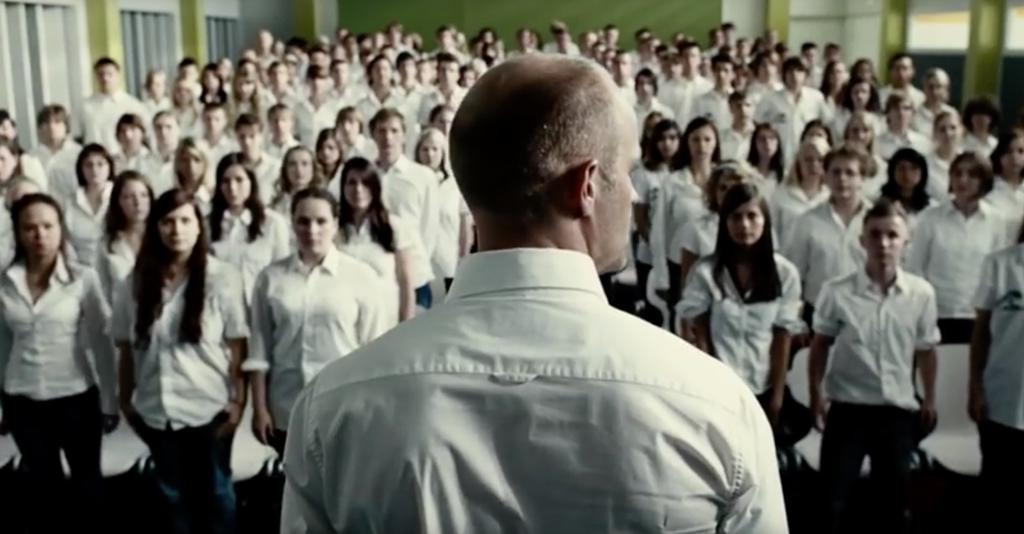Man står framför klass i vita skjortor.