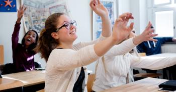 Elever sitter i bänkarna och sträcker upp händerna.