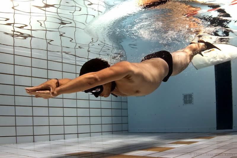 Man dyker ner under vattnet i en pool.