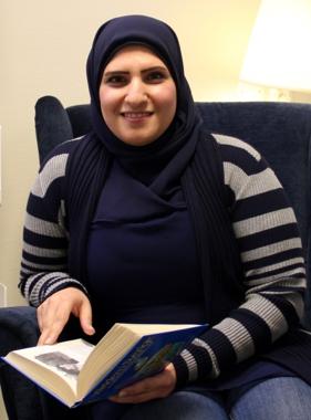 Amina sitter med bok.