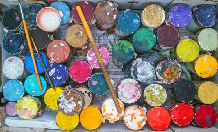 Burkar med olika färger och penslar.