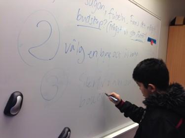 Elev skriver på tavla.