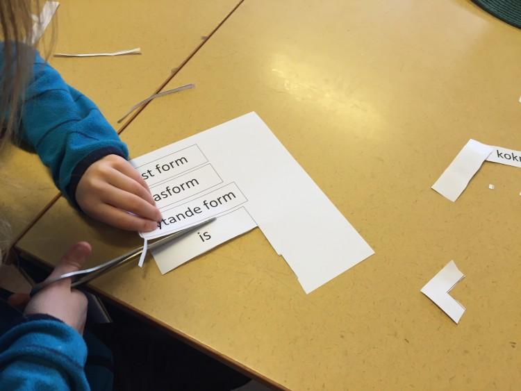 Elev klipper ut begrepp som står skrivna på lapp.