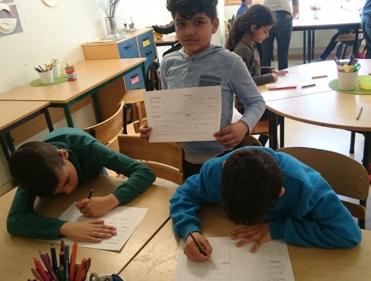 Tre elever sitter i sina bänkar och jobbar.
