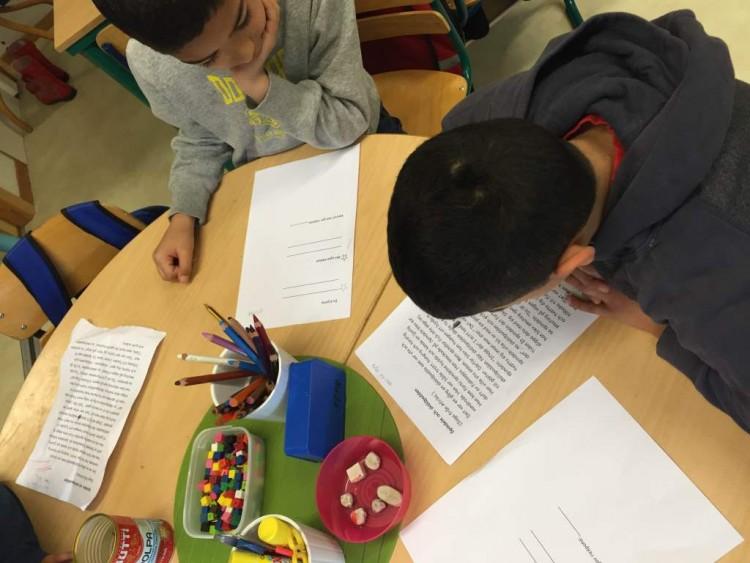 Barn sitter vid bänkarna och skriver.