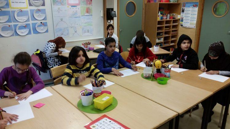 Barn sitter och jobbar vid sina bänkar.