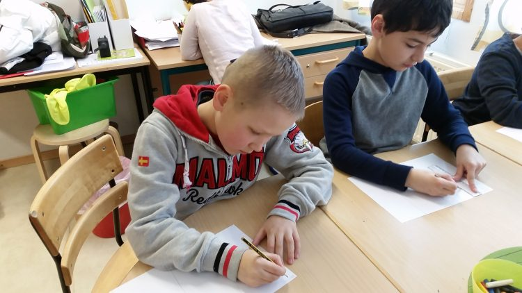 Barn sitter och skriver i sina bänkar.
