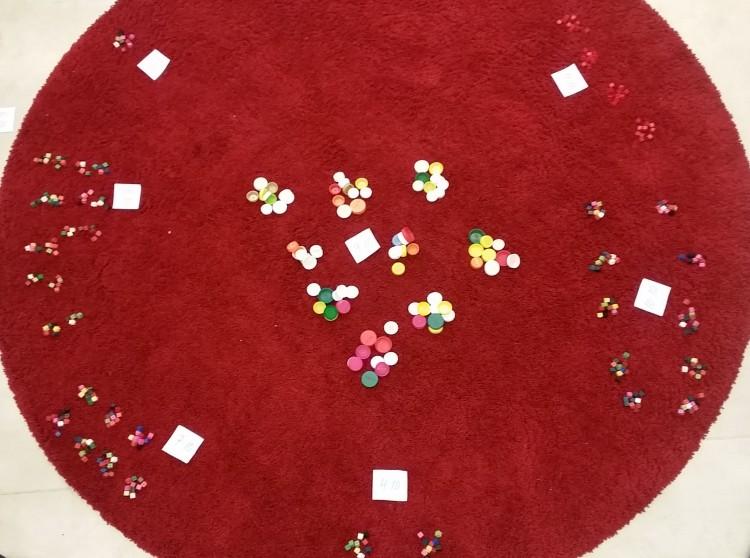 Färgglatt material ligger på röd rund matta.