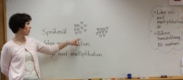 Pedagog står vid tavla och pekar på text.