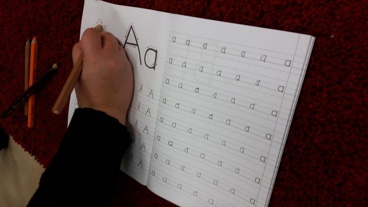 Barn skriver bokstaven a i häfte.