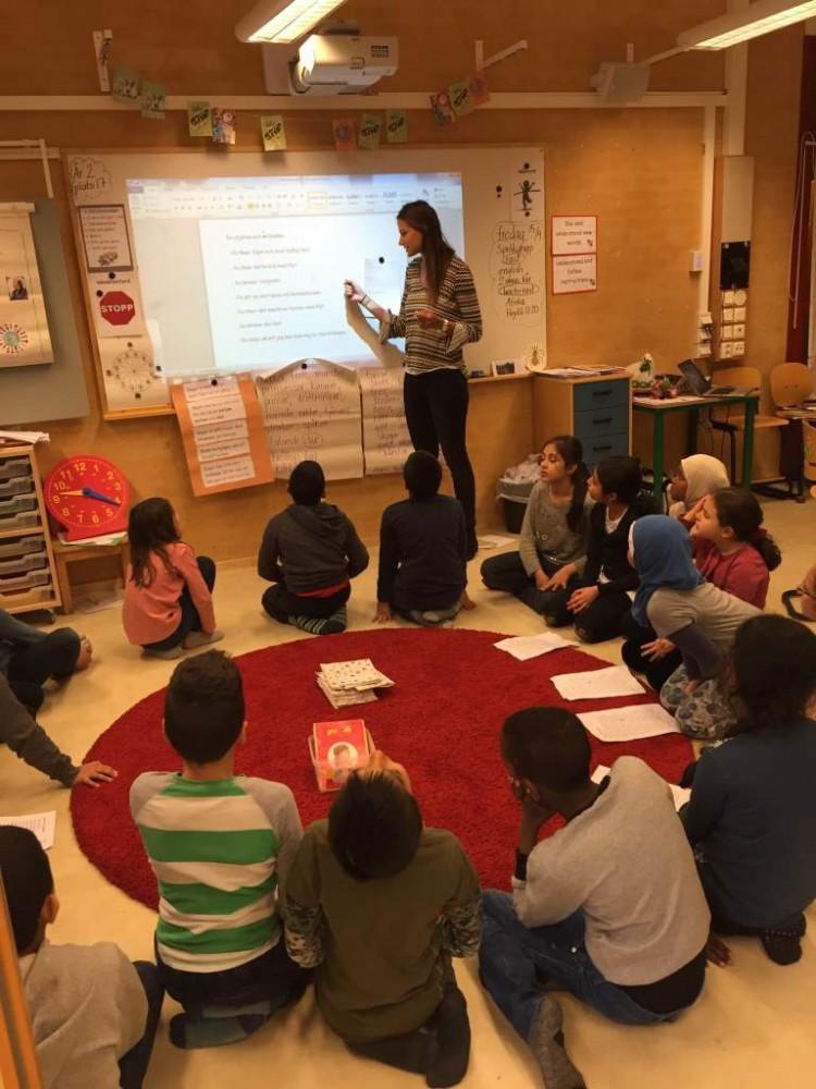 Barngrupp sitter på golvet och tittar på tavlan där pedagog visar.