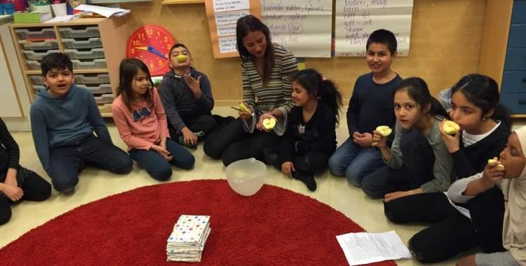 Barngrupp sitter på golvet och äter mellanmål.