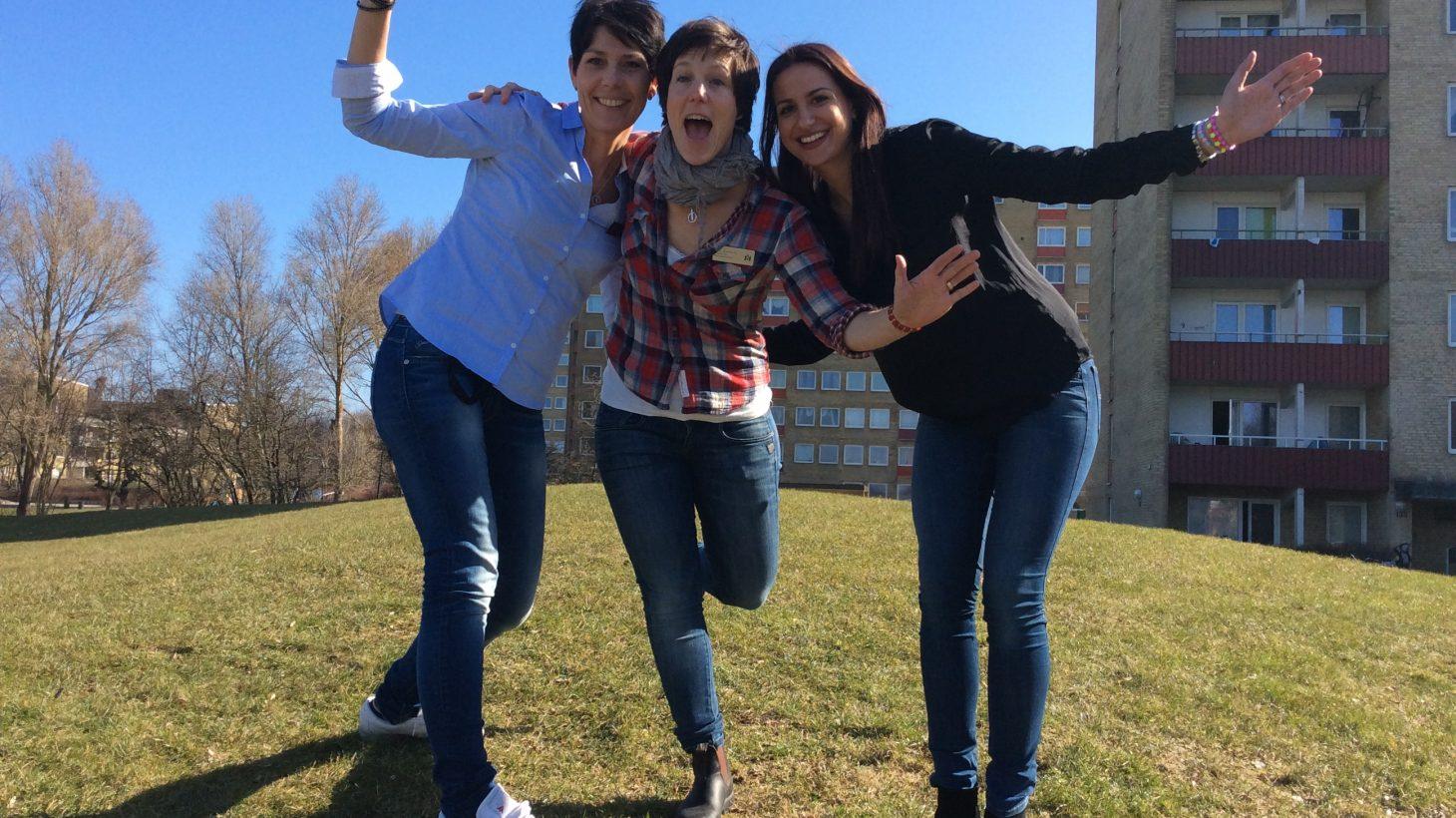 Tre kvinnor håller om varandra.