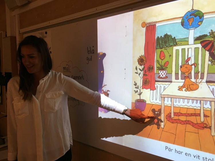 Kvinna pekar på presentation projicerad på tavla.
