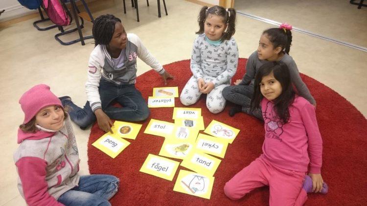 Elever sitter på golvet och arbetar.