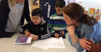 Två pedagoger hjälper elever.
