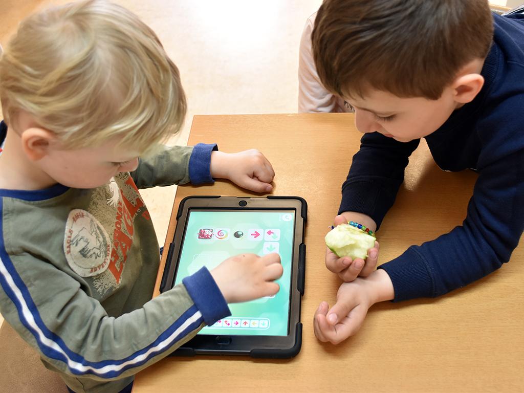 Två barn jobbar tillsammans på ipad.
