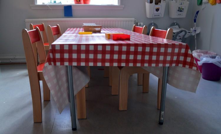 Litet bord och små stolar med rödrutig duk.
