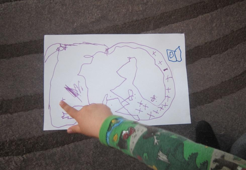 Barnhand pekar på teckning.