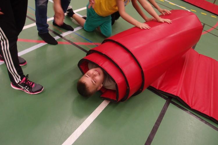 Elev rullas in i matta i gympasalen.