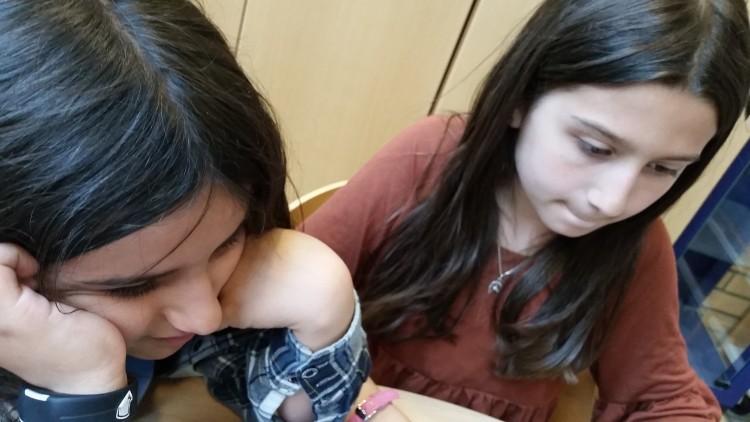 Två elever sitter i bänk.
