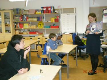 Kvinna håller upp bok framför elever i bänk.