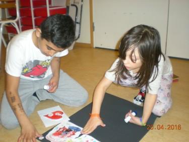 Två elever sitter på golvet och jobbar.