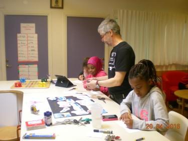 Pedagog tillsammans med elever som klipper och klistrar.