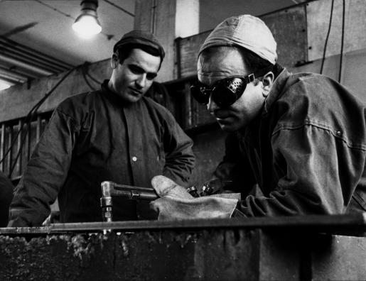 Två industriarbetare svetsar.