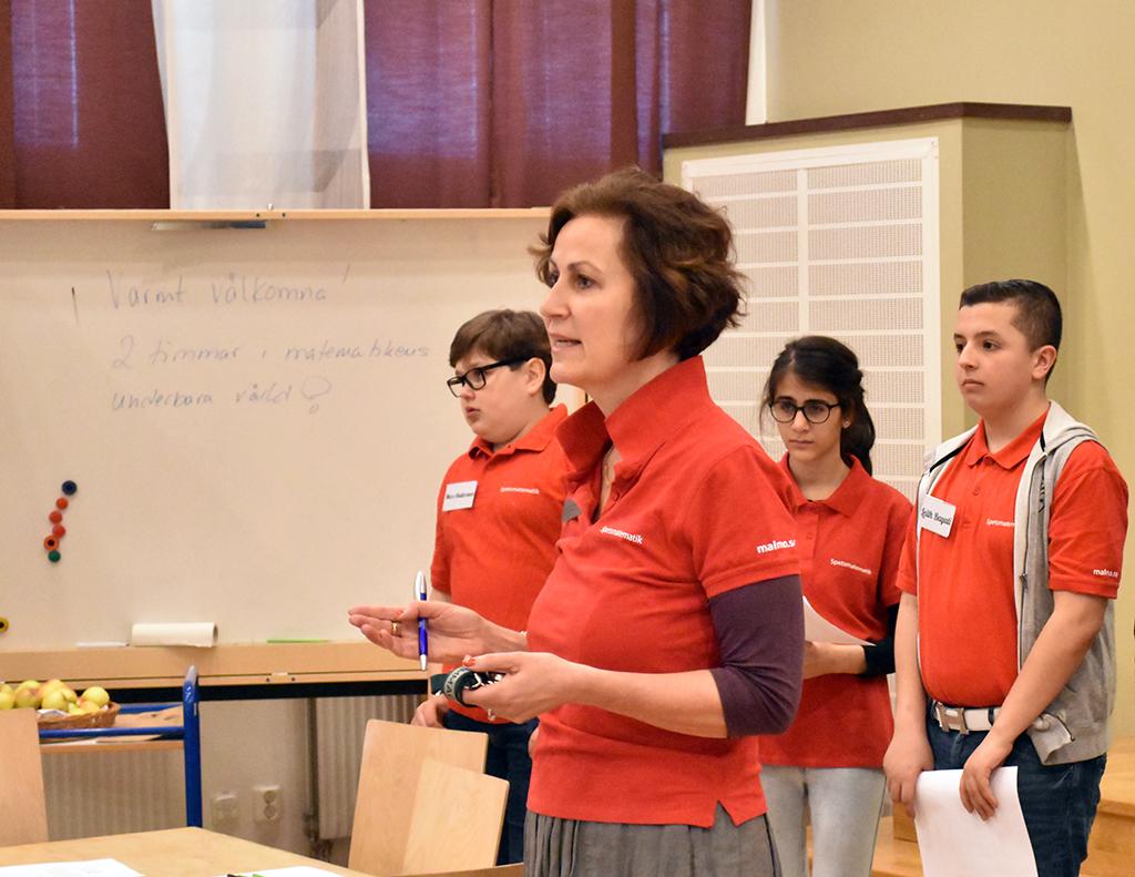 Lotta och tre elever står framför klass.