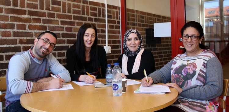 Tre studenter sitter vid bord.