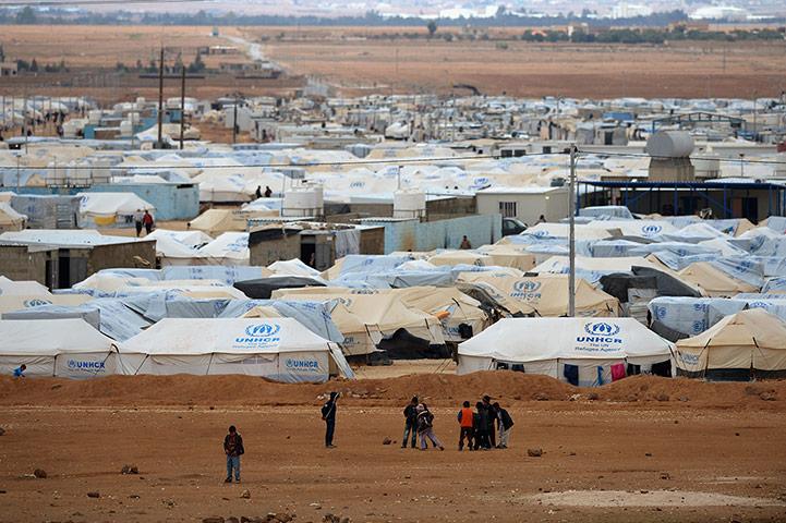 Flyktingläger med vita tält i öken.