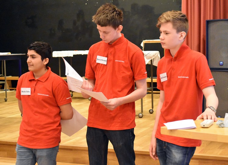 Tre elever står vid scen.
