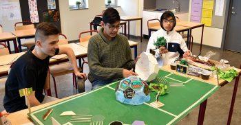 Tre elever visar upp modell.